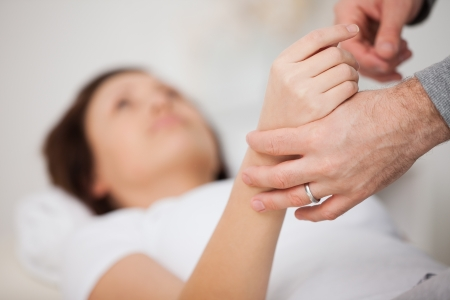 Hand of a woman being manipulated in a medical office Stock Photo