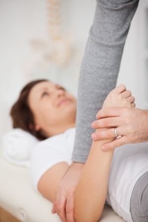 neuromuscular reeducation: Physiotherapist manipulating the arm of a patient in a room