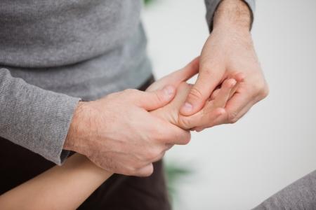 naprapathy: Physiotherapist massaging a hand indoors Stock Photo