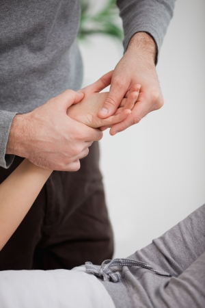 muscle retraining: Physiotherapist massaging the hand of a patient