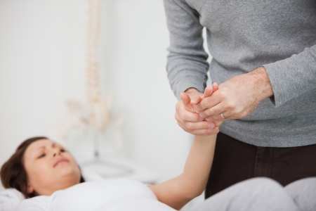 muscle retraining: Physiotherapist massaging a painful hand indoors