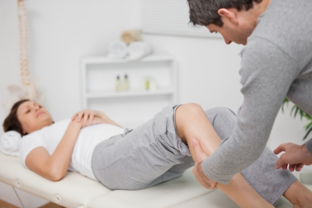 neuromuscular reeducation: Physiotherapist massaging a calf in a room Stock Photo
