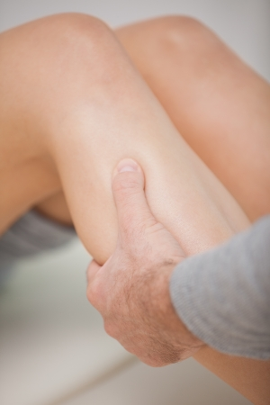 neuromuscular reeducation: Masseur massaging the calves of a patient in a room