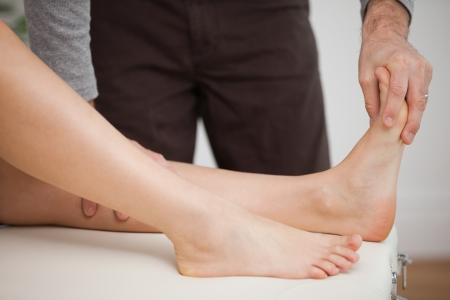 chiropodist: Chiropodist touching the foot of a patient in a room