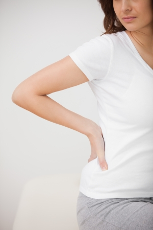 lumbar curve: Woman massaging her painful hip while sitting in a room