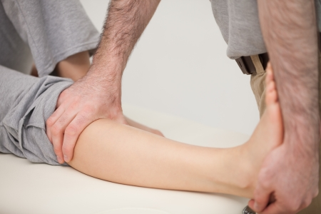 neuromuscular reeducation: Physiotherapist stretching the leg of a patient in a medical room