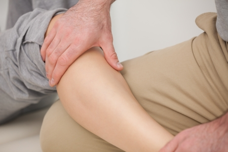 neuromuscular reeducation: Man massaging the calves of a woman indoors