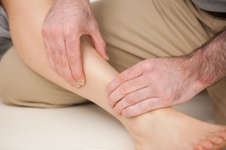 Physiotherapist massaging the shin bone indoors Stock Photo - 16207905