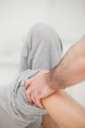 neuromuscular reeducation: Practitioner looking at the leg of his patient in a room