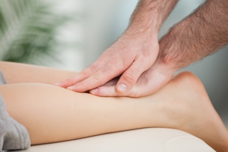 Physiotherapist massaging the calf of a woman in a room photo