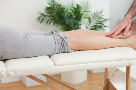 Physiotherapist massaging the legs of a woman in a physio room photo