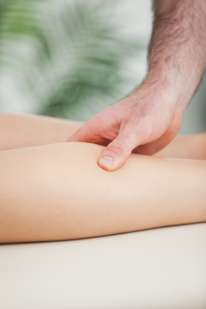 Close up of a man massaging the calf of a woman in a room Stock Photo - 16204394