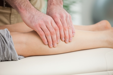 Woman lying forward while a man massaging her calf indoors Stock Photo - 16206904