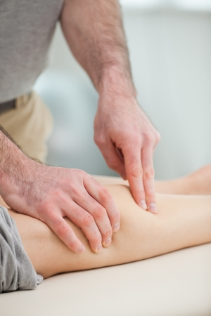 Physiotherapist pressing the calf of a patient in a room Stock Photo - 16206664