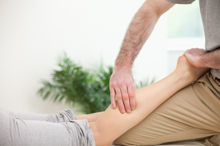 muscle retraining: Physiotherapist pressing a leg with his fingers in a room