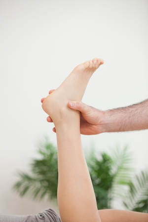neuromuscular reeducation: Doctor holding the foot of his patient in a room Stock Photo