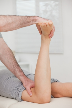 Physiotherapist bending the led of a woman in a room Stock Photo - 16206667
