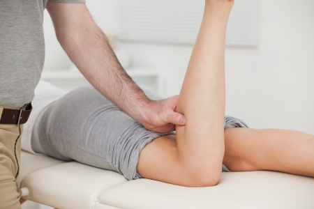 neuromuscular reeducation: Woman lying forward while a physiotherapist bends her leg indoors