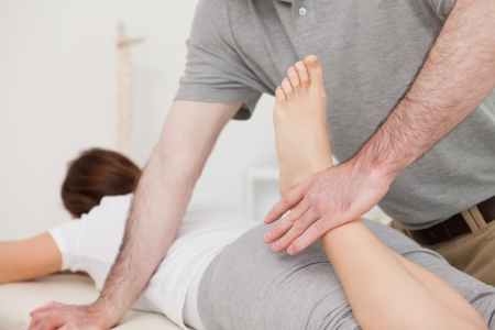 Physiotherapist bending the leg of his peaceful patient in a room Stock Photo - 16207406