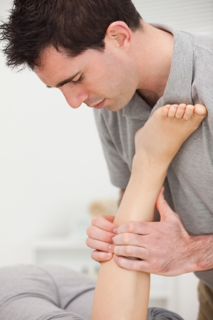 Woman lying while a physiotherapist is manipulating her leg indoors Stock Photo - 16207868