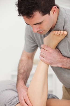 Physiotherapist manipulating the leg of a woman while she is lying in a room Stock Photo - 16207457