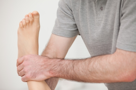 muscle retraining: Close-up of a physiotherapist manipulating an ankle in a room