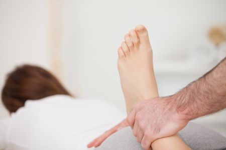 Woman lying forward while a physio manipulates her foot in a room Stock Photo - 16203523