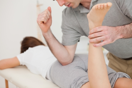 Woman lying while being massaged by her doctor in a room Stock Photo - 16206980