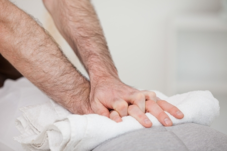 spinal disc herniation: Close-up of a masseur massing a woman indoors Stock Photo