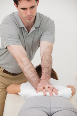 sacroiliac joint: Woman lying forward while a physiotherapist massaging her back in a room