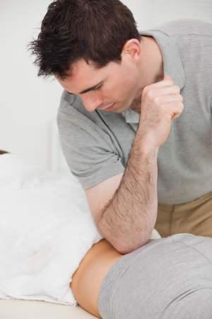 coccyx pain: Physiotherapist massaging the back of a woman with his elbow in a room Stock Photo