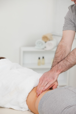 sacroiliac joint: Woman lying while a physiotherapist is massaging her back in a physio room