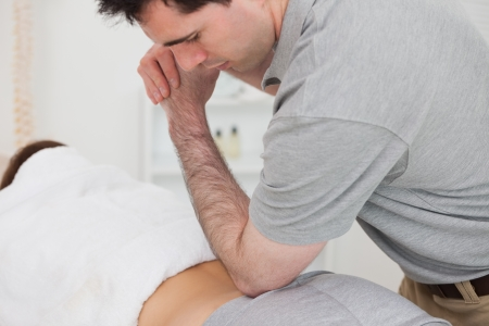 Woman lying forward while a physiotherapist is massaging her back in a physio room Stock Photo - 16208067