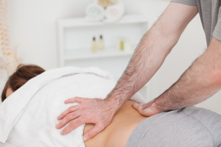 Masseur massaging the back of a woman in a room photo