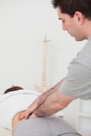 Physiotherapist massaging the lower part of the back of his patient in a room photo