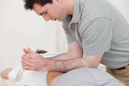 Physiotherapist massaging the back of a patient with his forearms in a room Stock Photo - 16208868