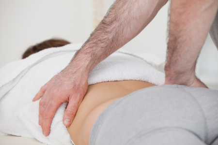 stenosis: Close-up of a physiotherapist massaging a back in a physio room Stock Photo