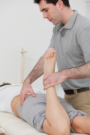 Woman lying while a physiotherapist is bending her leg in a room Stock Photo - 16208024