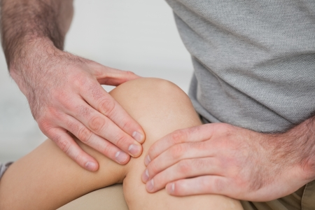 Physiotherapist massaging a painful knee in a room photo