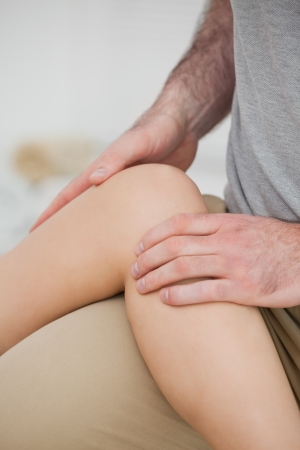 Physiotherapist folding a leg over her thigh in a physio room photo