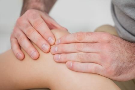 tendones: Primer plano de manos que hacen un masaje en la rodilla en una habitaci�n