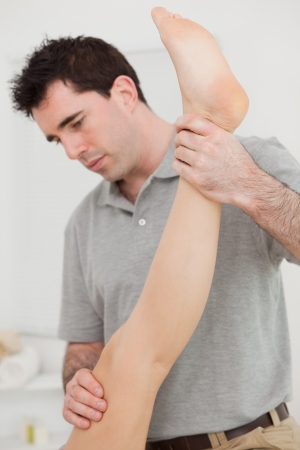 joint mobilization: Chiropractor extending the leg of a patient in a room