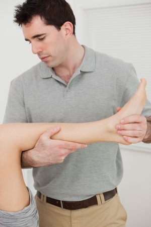 muscle retraining: Physio folding the leg of a patient in a physio room Stock Photo