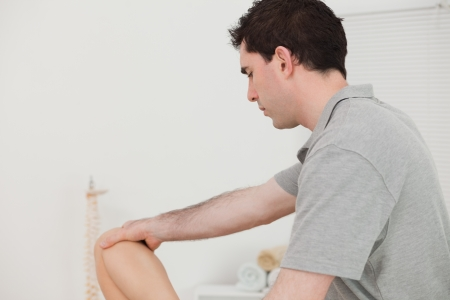 naprapathy: Serious chiropractor holding the knee of a patient in a physio room