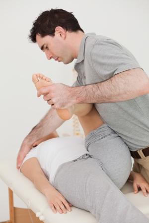 osteopata: Oste�pata grave estirando la pierna de su paciente en una habitaci�n
