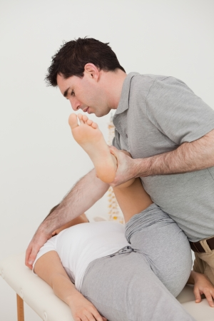 Woman lying while a physio moving her leg in a room Stock Photo - 16207608