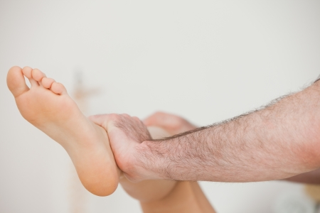 joint mobilization: Close-up of a physiotherapist moving a leg in a room Stock Photo