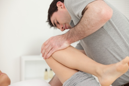 mobilization: Woman lying while a physiotherapist folded her leg on her chest in a physio room