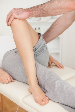 fysiotherapie: Fysiotherapeut het oversteken van de poot van zijn patiënt in een fysio kamer Stockfoto