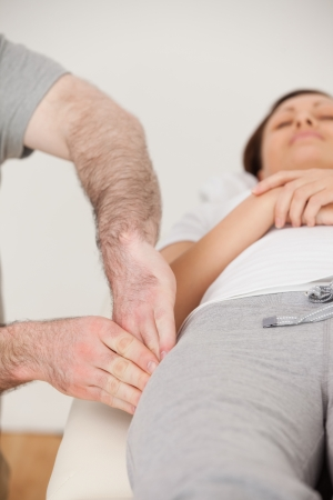 tensor: Physiotherapist massaging the thigh of his peaceful patient in a room Stock Photo